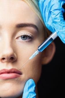 Женщина получает инъекцию на губах
