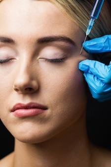 Женщина получает инъекцию ботокса на лоб