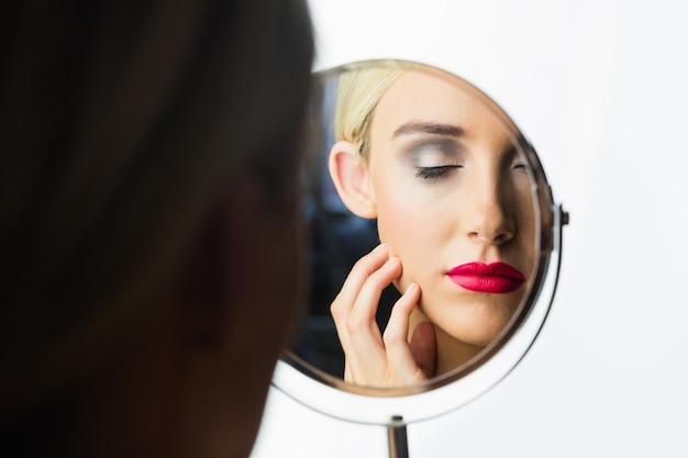 Портрет женщины, которая смотрит на нее в зеркало