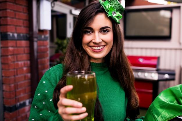 緑のパイントを保持している変装した女性