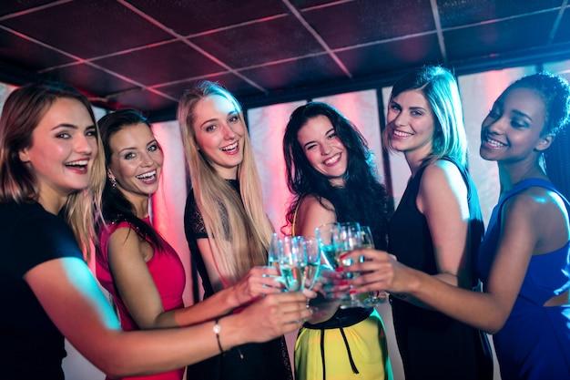 Группа улыбающихся друзей тостов бокал шампанского