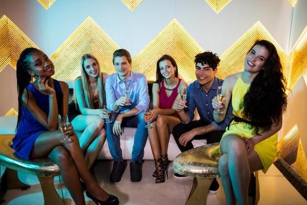 Группа улыбающихся друзей с бокалом шампанского в баре