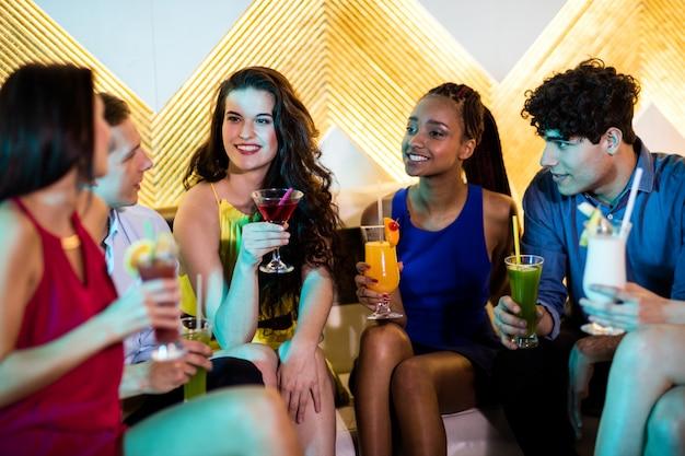 Группа улыбающихся друзей, взаимодействующих во время коктейля