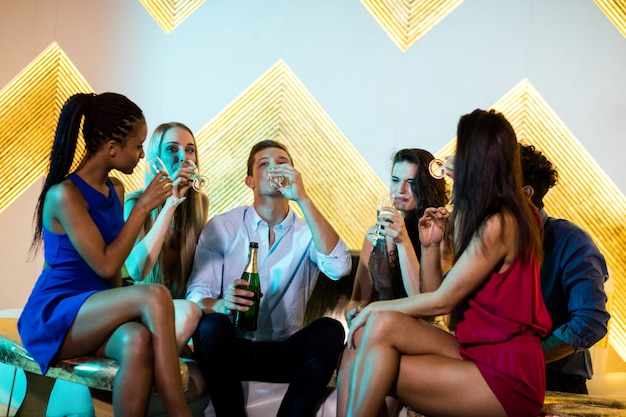 Группа улыбающихся друзей, сидя на диване и с бокалами шампанского
