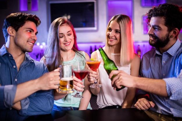Группа друзей тостов коктейль, бутылка пива и бокал пива на барной стойке