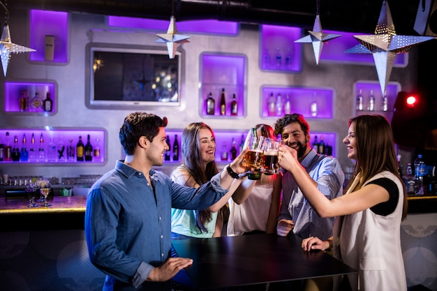Группа друзей поджаривания пивные бокалы за барной стойкой
