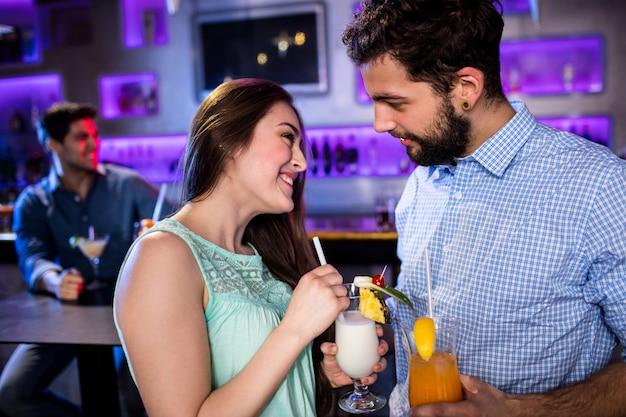 Улыбающиеся друзья общаются друг с другом за барной стойкой за коктейлем