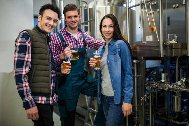 Пивовары держат пивные бокалы на пивоваренном заводе