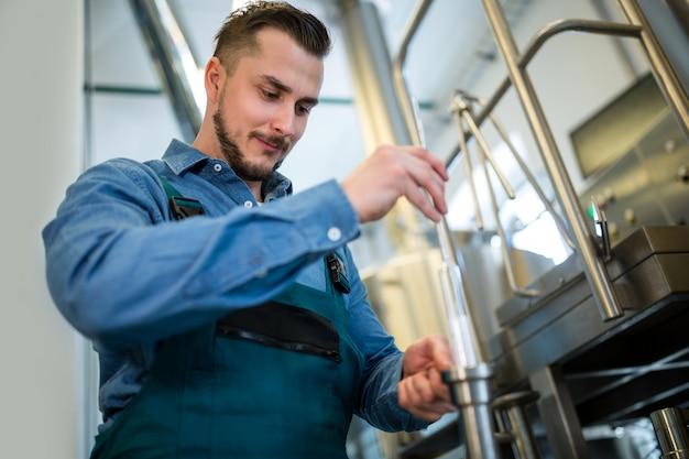 Пивовар проверяет пиво с помощью ареометра