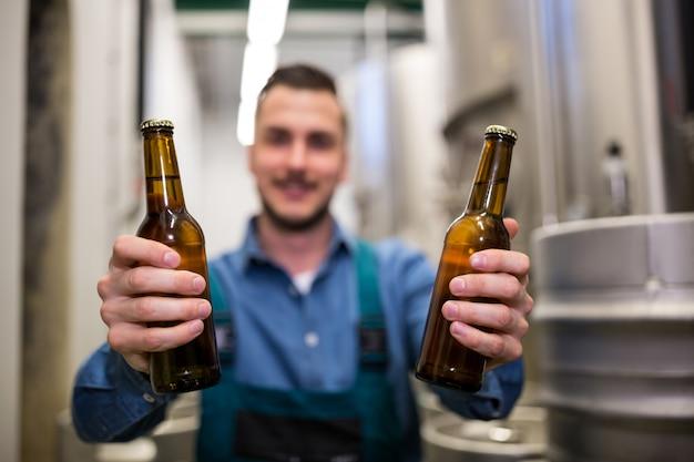 Пивовар держит две бутылки пива