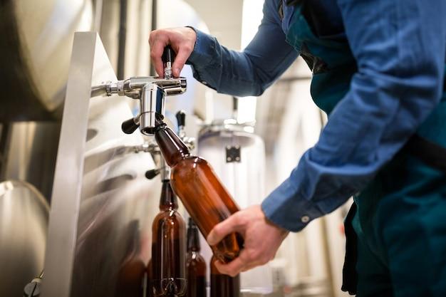 Пивовар разливает пиво в бутылку