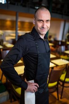 レストランに立っている幸せなウェイター