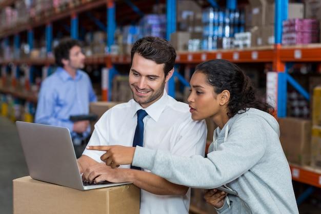 Улыбающиеся рабочие, указывающие на ноутбук