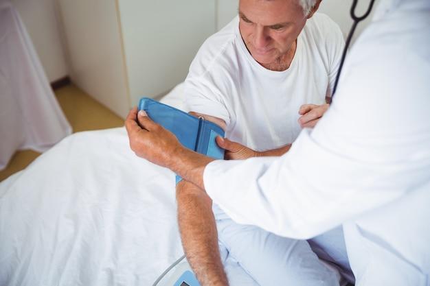 Медсестра, измерения кровяного давления старшего человека
