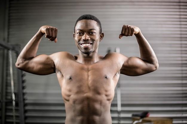 アスレチック男のジムで筋肉を示す