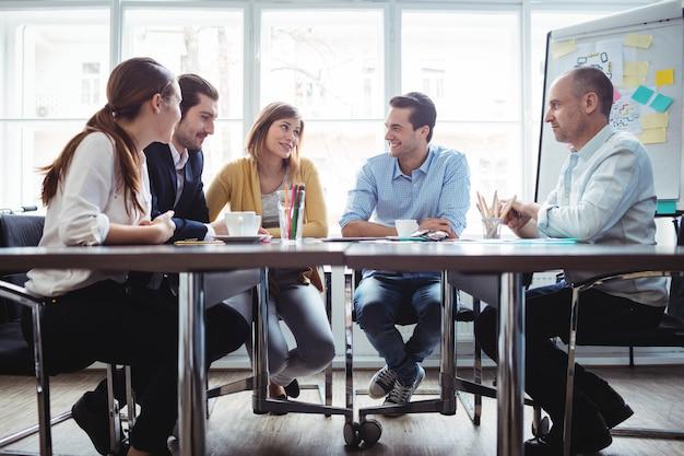 会議室で議論する同僚