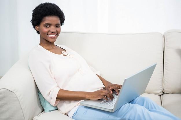 妊娠中の女性がソファの上にラップトップを使用して