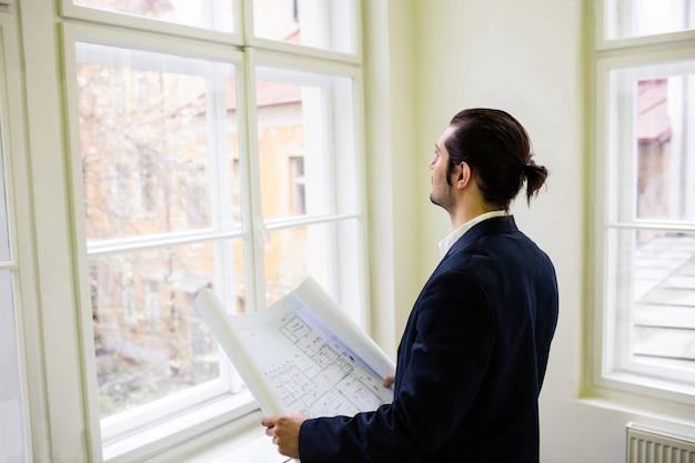 Дизайнер интерьера с планом, глядя через окно