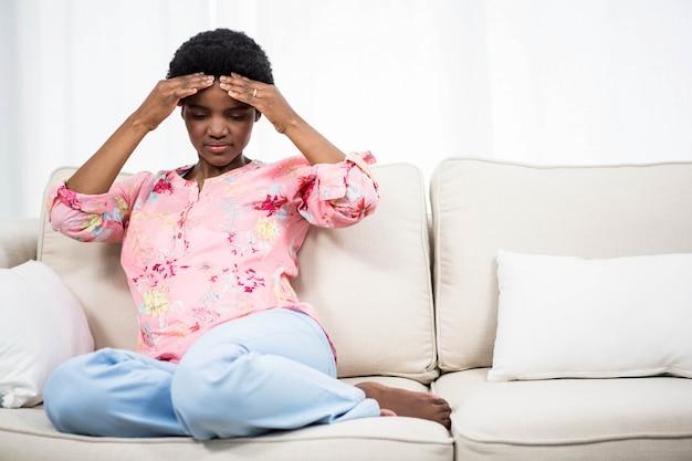 ソファの上に頭痛と妊娠中の女性