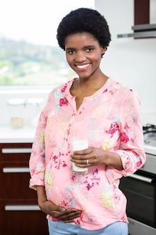 Беременная женщина пьет стакан молока на кухне