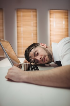 オフィスで寝ている若い男