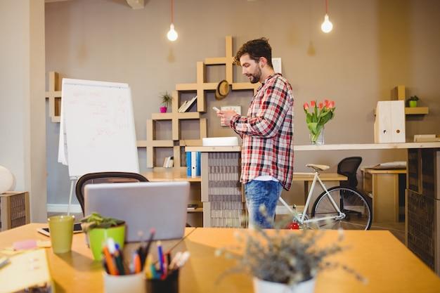 Мужской графический дизайнер с помощью мобильного телефона