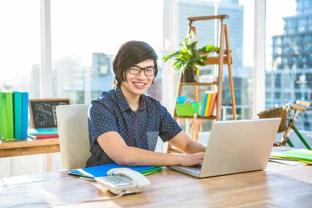 オフィスでラップトップを使用して笑顔の流行に敏感なビジネスマン