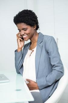 Беременная деловая женщина разговаривает по телефону в офисе