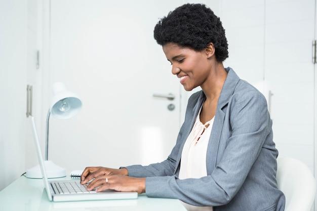 妊娠中の女性実業家のオフィスでラップトップを使用して