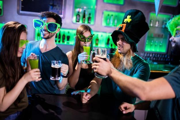 ビールジョッキとドリンクグラスを乾杯の友人のグループ