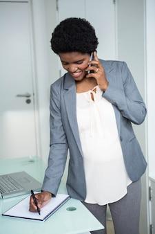 Беременная коммерсантка писать на тетради в офисе