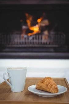 リビングルームのテーブルの上のコーヒーとクロワッサンのビュー
