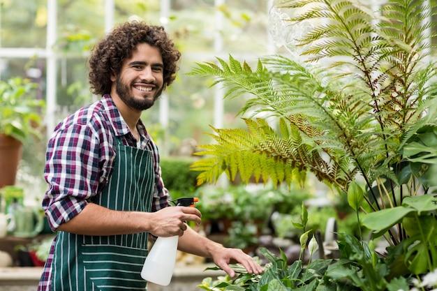 Счастливый мужчина садовник поливает растения