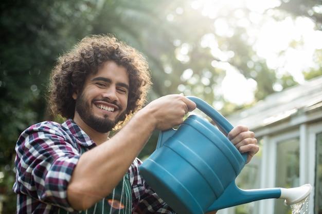 Счастливый садовник поливает за пределами теплицы