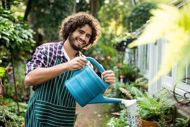 Уверенный мужчина садовник поливает горшечные растения