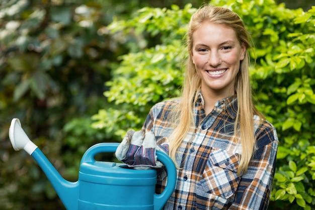 Уверенная женщина-садовник держит лейку