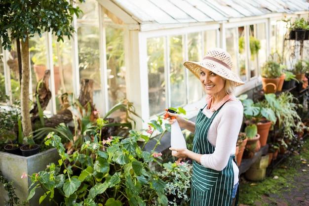 Счастливая женщина садовник поливает растения