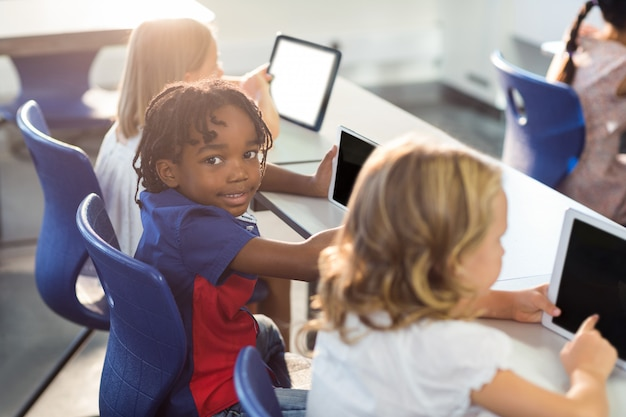デジタルタブレットを使用してクラスメートと微笑む少年