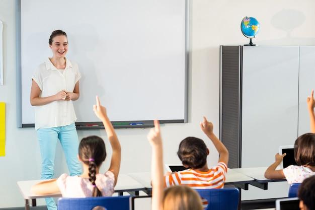Учитель смотрит на студентов, поднимающих руки