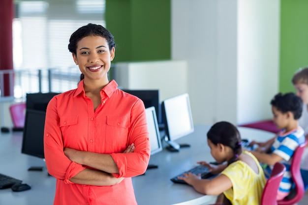 自信を持って女性教師が腕を組んでコンピューター室に立っています。