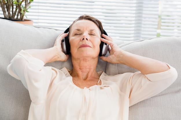 Крупный план зрелой женщины, слушая музыку