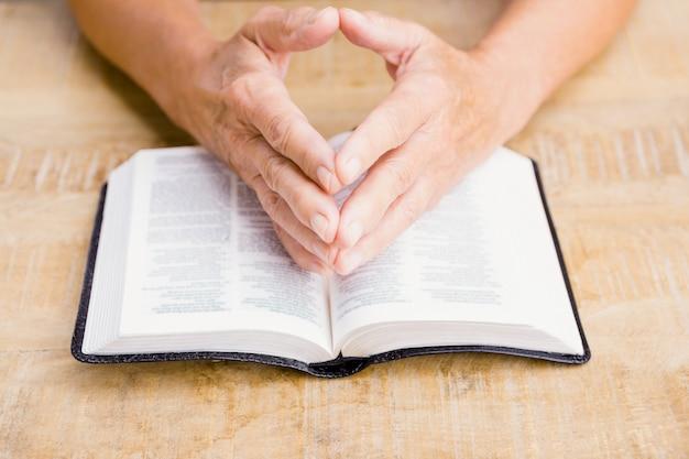 テーブルで聖書を持つ人