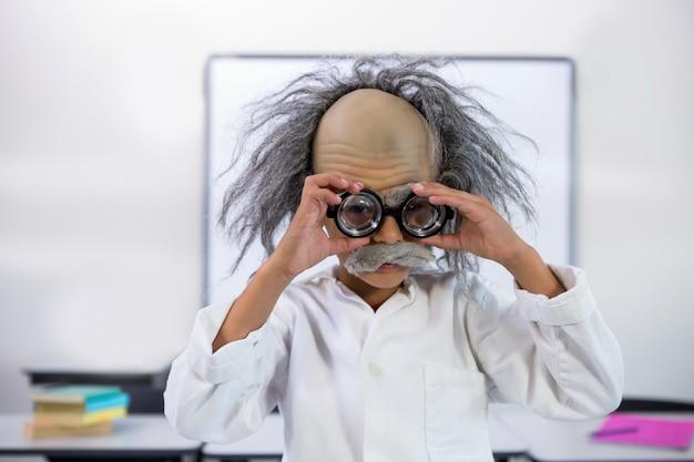 Мальчик одет как ученый, держа очки в классе