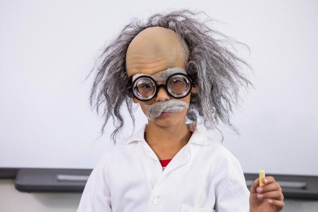 Мальчик одет как ученый, держа бумагу в классе