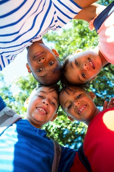 ハドルを形成する幸せな子供たちの低角度の肖像画