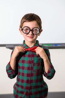 Мальчик связывает лук стоя в классе