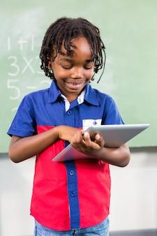 教室でデジタルタブレットを使用して微笑む少年