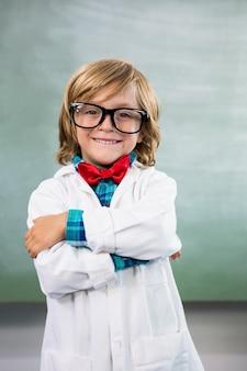 Улыбающийся мальчик одет как ученый, стоя в классе