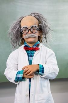 Мальчик одет как ученый позирует на доске