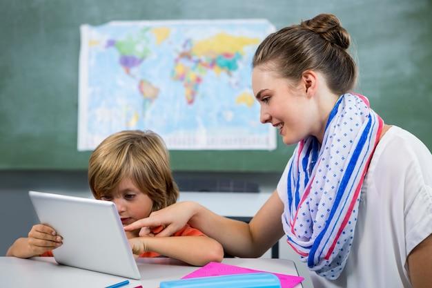 デジタルタブレットを使用して少年を助ける笑顔の先生